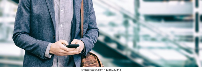 Business man texting using phone walking on travel commute at office background banner panorama. Businessman hand holding cellphone device technology. Mobile 5g network