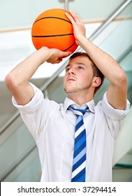 Business man throwing a basketball indoors