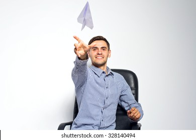 Business man throwing a paper plane on white background