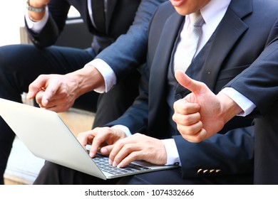 the business man thumb up after his team work present work on laptop