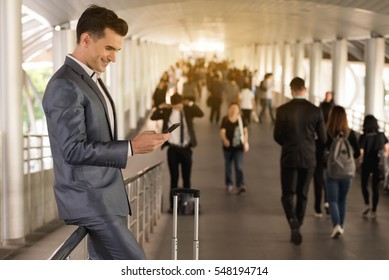 Business man traveling use smart phone on the walk way with crowded people in background