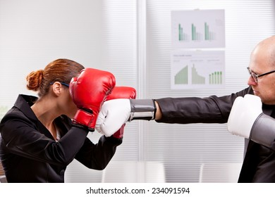business man trying to punch a business woman in a box match