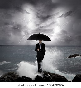 Business man under an umbrella standing on a rock in the sea with lightning sky, business concept
