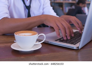 Business man use laptop to do the job with coffee and smartphone on  the wood table