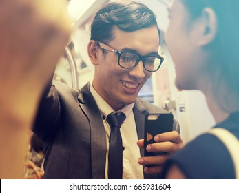business man use the smart phone in the subway train