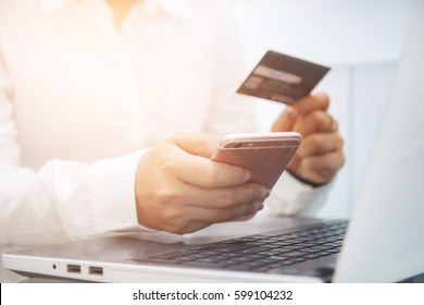 Business man use smart-phone and holding credit card for pay money by online shopping website with laptop computer. technology. online payment.