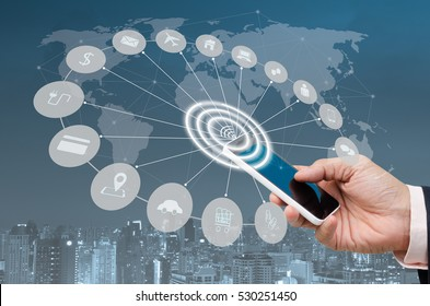 Business man using blue screen mobile smartphone and city night in blue tone background with digital alarm wifi and web icons, internet of things IOT, smart city concept