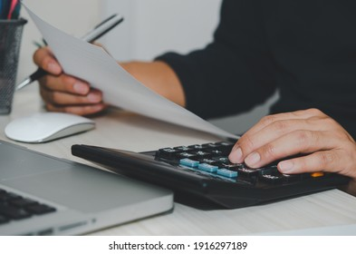 Business Man using calculator at a desk. Business finance, tax, and investment concepts.