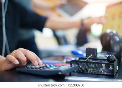 Business man using calculator with doing finance at his office.
