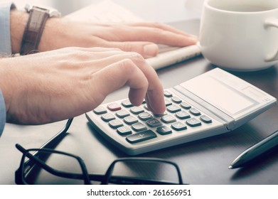 Business man using a calculator at his desk