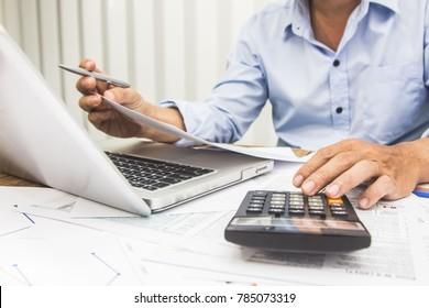 Geschäftsmann, der den Rechner benutzt und Geld für die Berechnung der Steuer im Büro hält.
