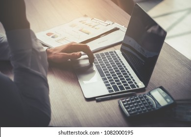 Business man is using computer on wooden table with calculator and financial accounting objects