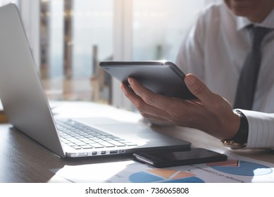 Business man using digital tablet analyzes business data, busy working on laptop computer with smart phone and business report on office desk, business strategy analysis concept, close up
