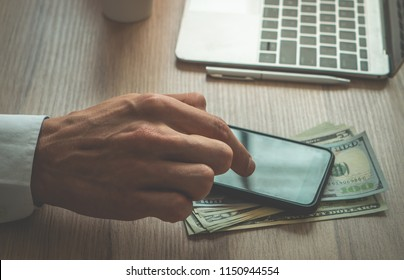 Business man using finger to use mobile phone on working desk