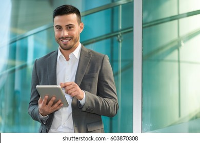 Business man using his digital tablet near a glass wall