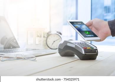 Ein Geschäftsmann, der sein Handy nutzt, um eine drahtlose Zahlung mit EDC-Maschine oder Kreditkartenterminal zu machen. Mobile Zahlungskonzept mit gefälschter Kreditkarte.
