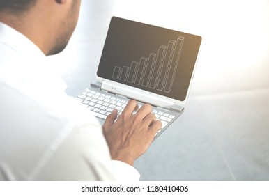 Business man is using the laptop with candlestick chart icon for marketing concept