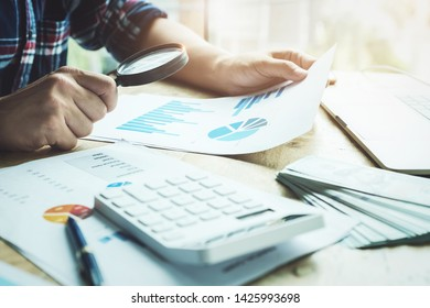 Business man using magnifying to review balance sheet annual with using calculator and laptop computer to calculating budget. audit and Check integrity before investment concept.