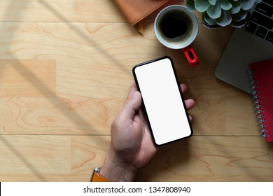 Business man using mobile phone on wood workspace