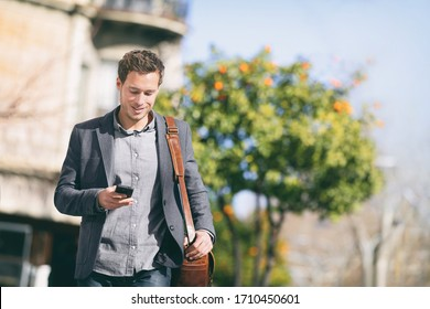 Business man using mobile phone walking in city street commuting to work with blazer and messenger bag texting on smartphone. Young businessman urban lifestyle.