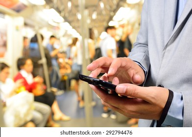 Business Man using Mobile Phone in Train or Subway