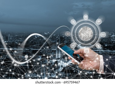 Business man using mobile smart phone with internet network globalization, web icons on screen on cityscape background, omnichannel, multichannel marketing, e commerce, internet of things IoT concept