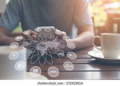 Business man using  mobile smartphone at home or coffee shop with internet web icons, globalization online shopping, e business, internet of things IOT, omnichannel or multichannel marketing concept.
