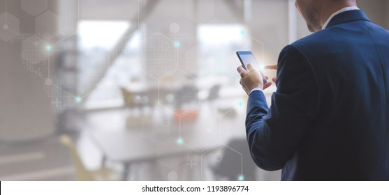 Business man using smart phone on interior office space with futuristic technology connection shape over the network connection background.