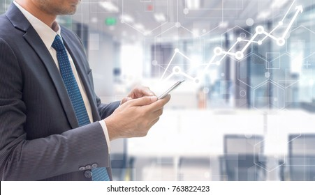 Business man using smart phone on futuristic technology connection shape over the motion interior space background with graph rise up.Concept of business people use technology.