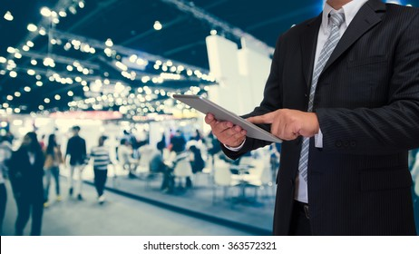 business man using tablet with blurry event background
