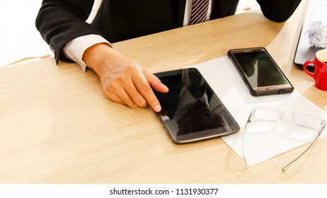 Business man using tablet and mobile phone with paper on office desk