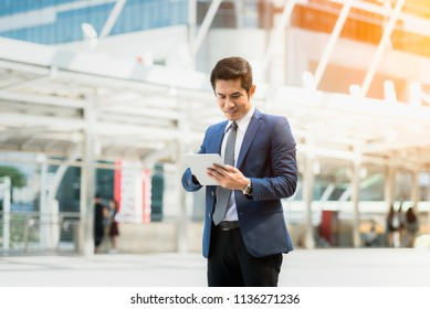 Business man using tablet and working outside office behind city background. Concept Businessman lifestyle.
