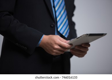 business man using touchscreen tablet device in business suit isolated in studio