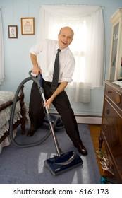 Business man vacuuming bedroom carpet