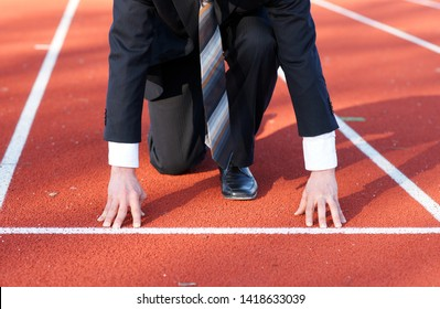 Business man waiting for start signal to run on the competition running track