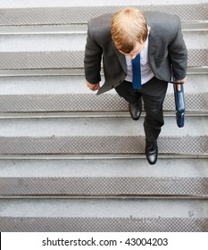 A business man walking down some steps