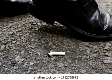 Business man walking near littered cigarette in asphalt street