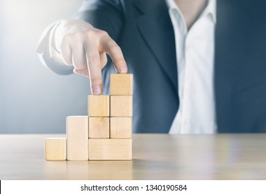 Business man walking up next step with fingers on career ladder made from wooden blocks; career or achievement concept, blue toned with ligth flare