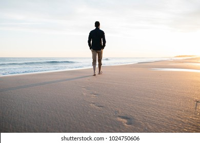 Business man walking on beach at sunset, after work. Relax time.