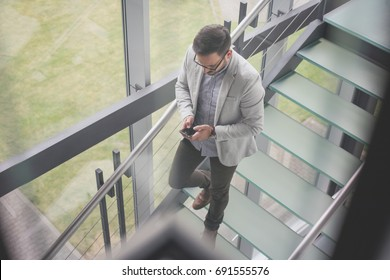 Business man walking on the stairs of business building. Business man checking e mail.
