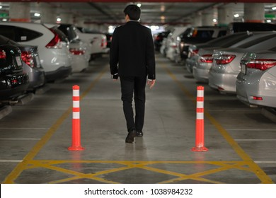 Business man walking on walk way in car park  of airport parking lot.
