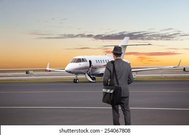 Business man walking toward a private jet