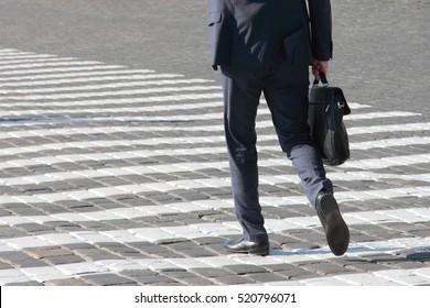 business man walks on a pedestrian crossing
