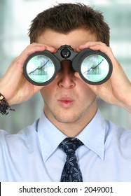 business man watching his business finances grow - there are column graphs on the reflections of the lenses