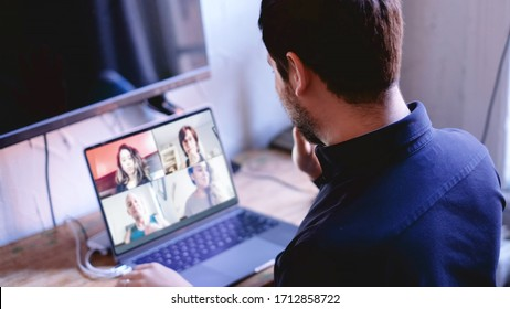 Business man waving at screen during virtual call meeting with his work teammates.  COVID-19 coronavirus work from home concept.