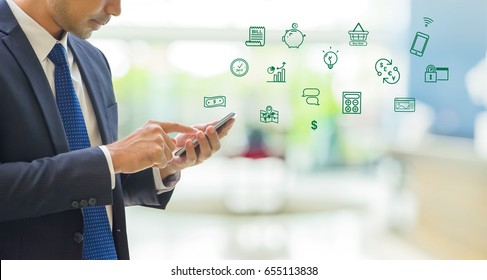 Business man wear suit using mobile phone to pay on mobile banking features icon with blur office background with bokeh light,fintech technology concept.