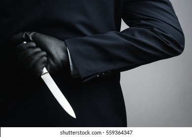Business man wearing black glove and holding knife on white background