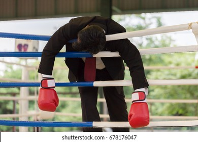 Business man wearing boxing glove loser Knock-out and body hanging on the rope feeling so stressed and tried,Business failed and loss concept