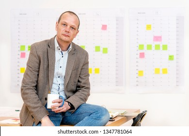 Business man, wearing a brown jacket and holding a coffee cup, sitting on a conference table in front of a wall with a planning board, covered with sticky notes