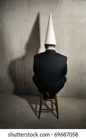 Business man wearing a dunce cap